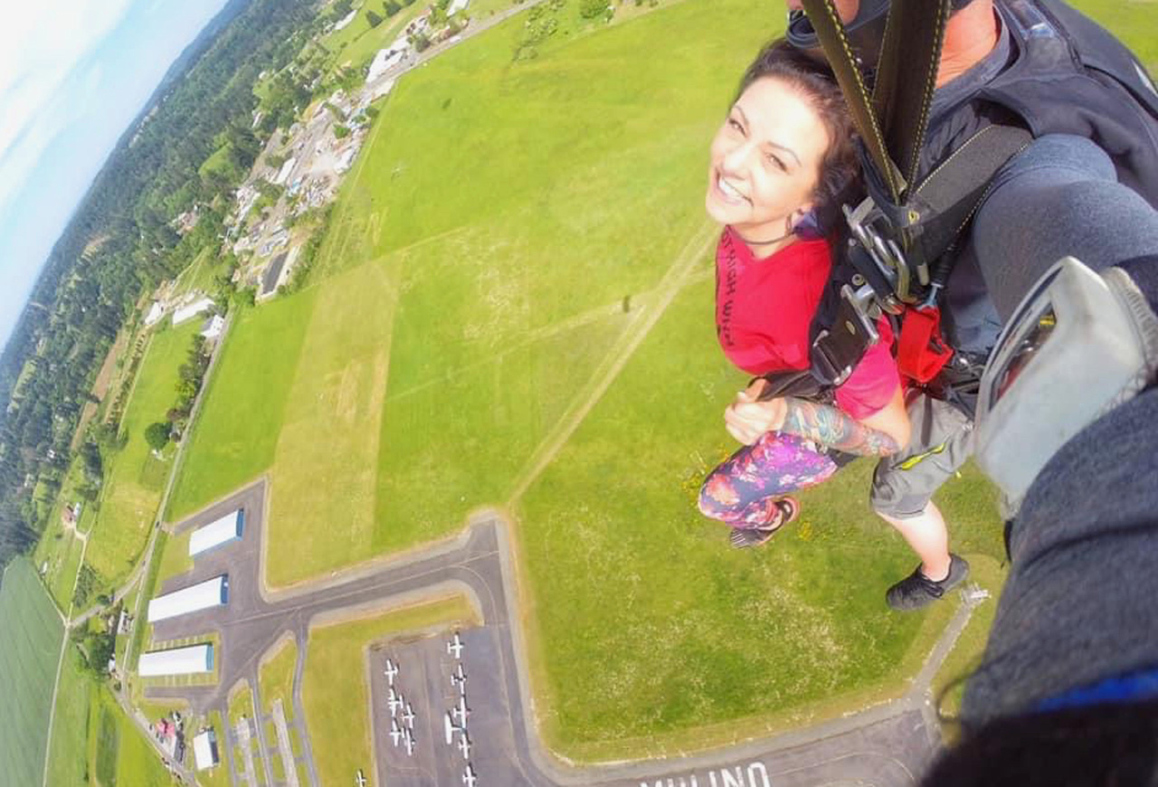 Happy female tandem skydiving student under canopy above landing area at PNW Skydiving