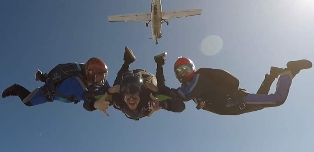 AFF student in freefall being assisted by two instructors at PNW Skydiving