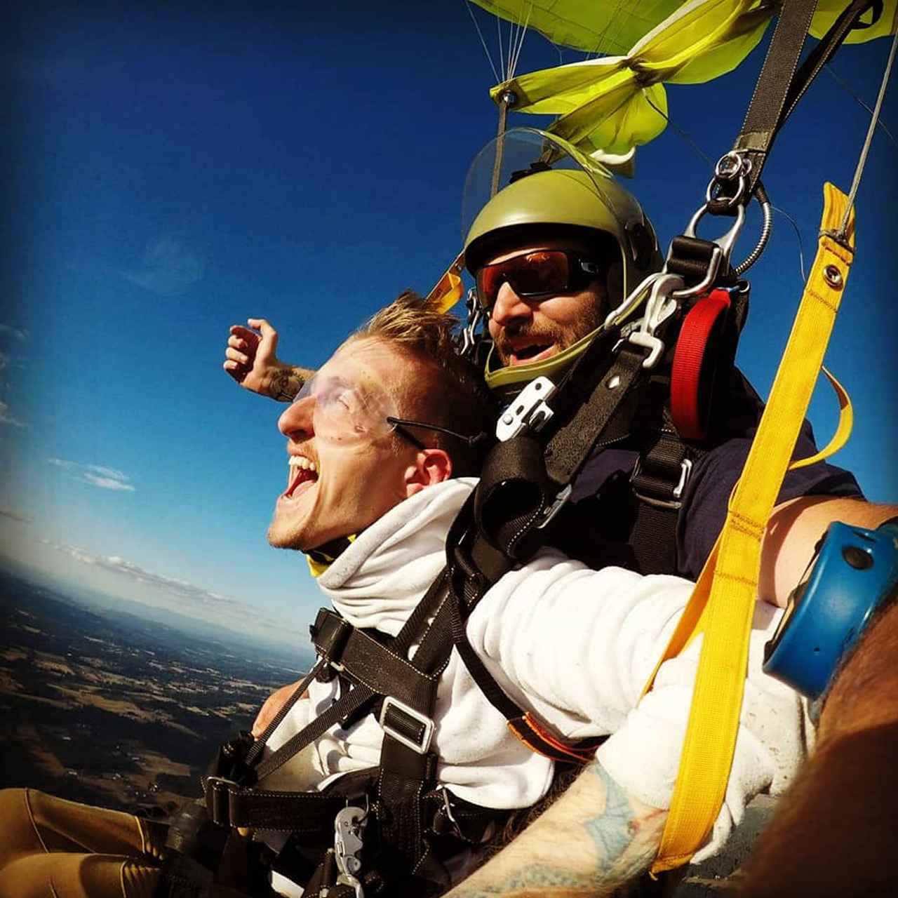 Male tandem skydiving student and instructor smiling under canopy above PNW Skydiving in Oregon