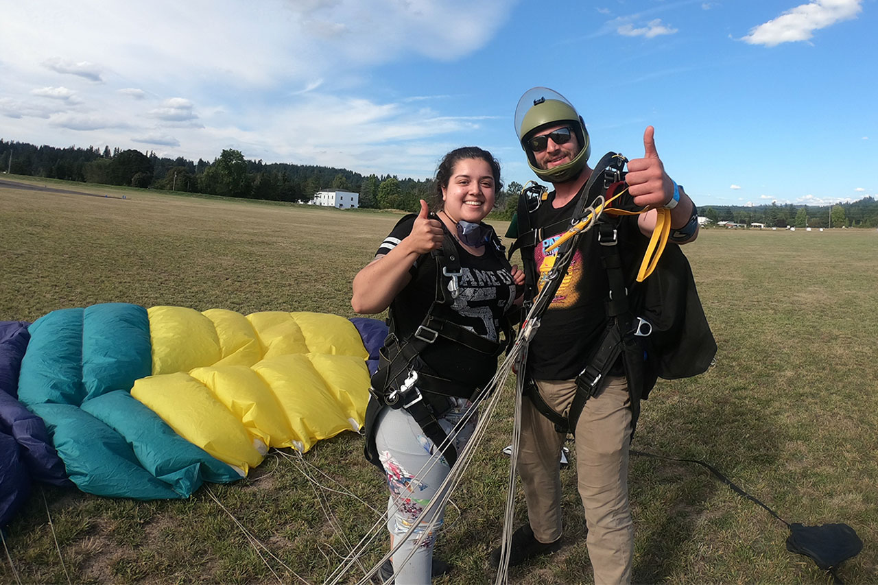 young girl gives thumbs up in landing area after skydive