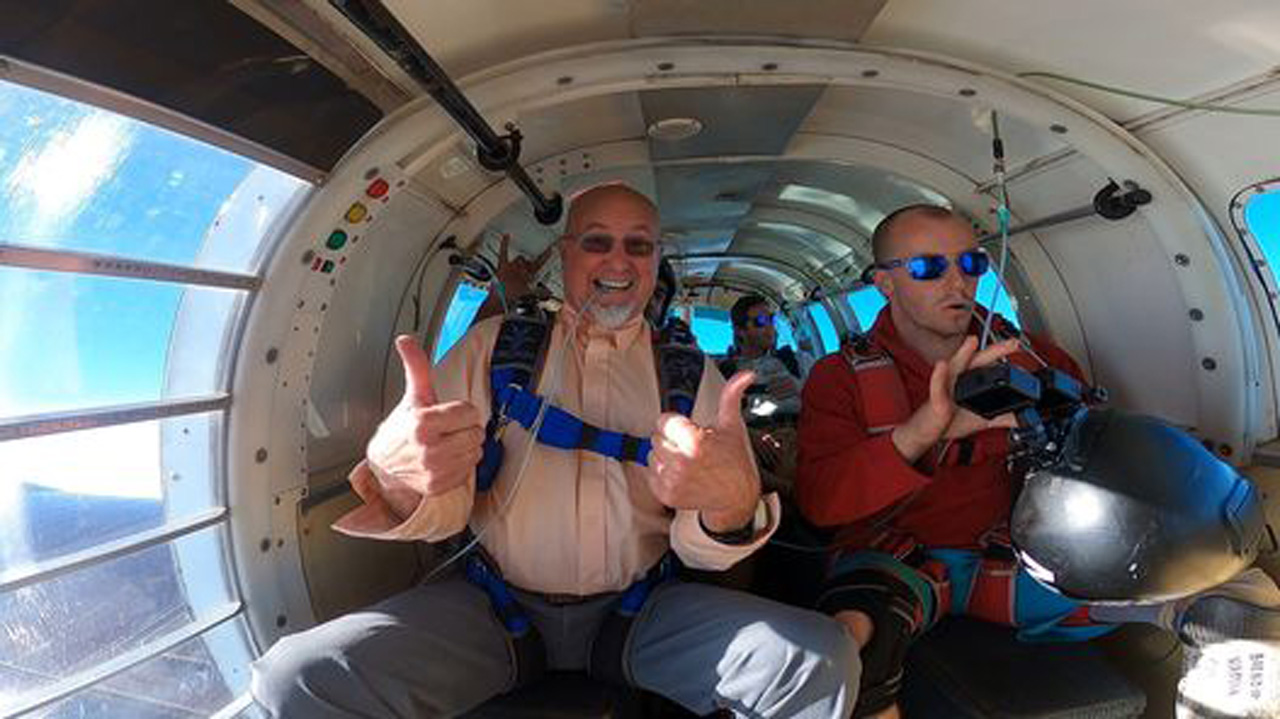 Older male tandem skydiving student in aircraft giving thumbs up at PNW Skydiving Center near Portland, OR