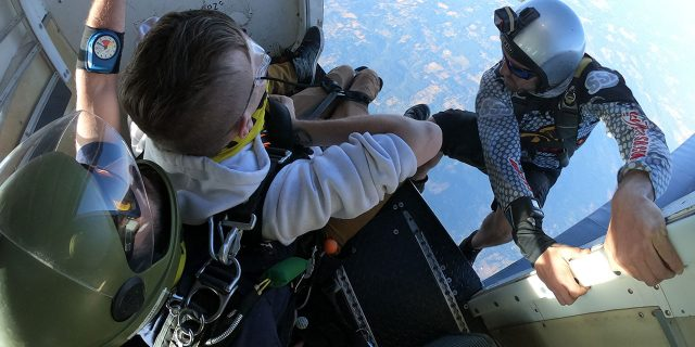 camera flyer perches on side of aircraft as tandem student prepares to jump