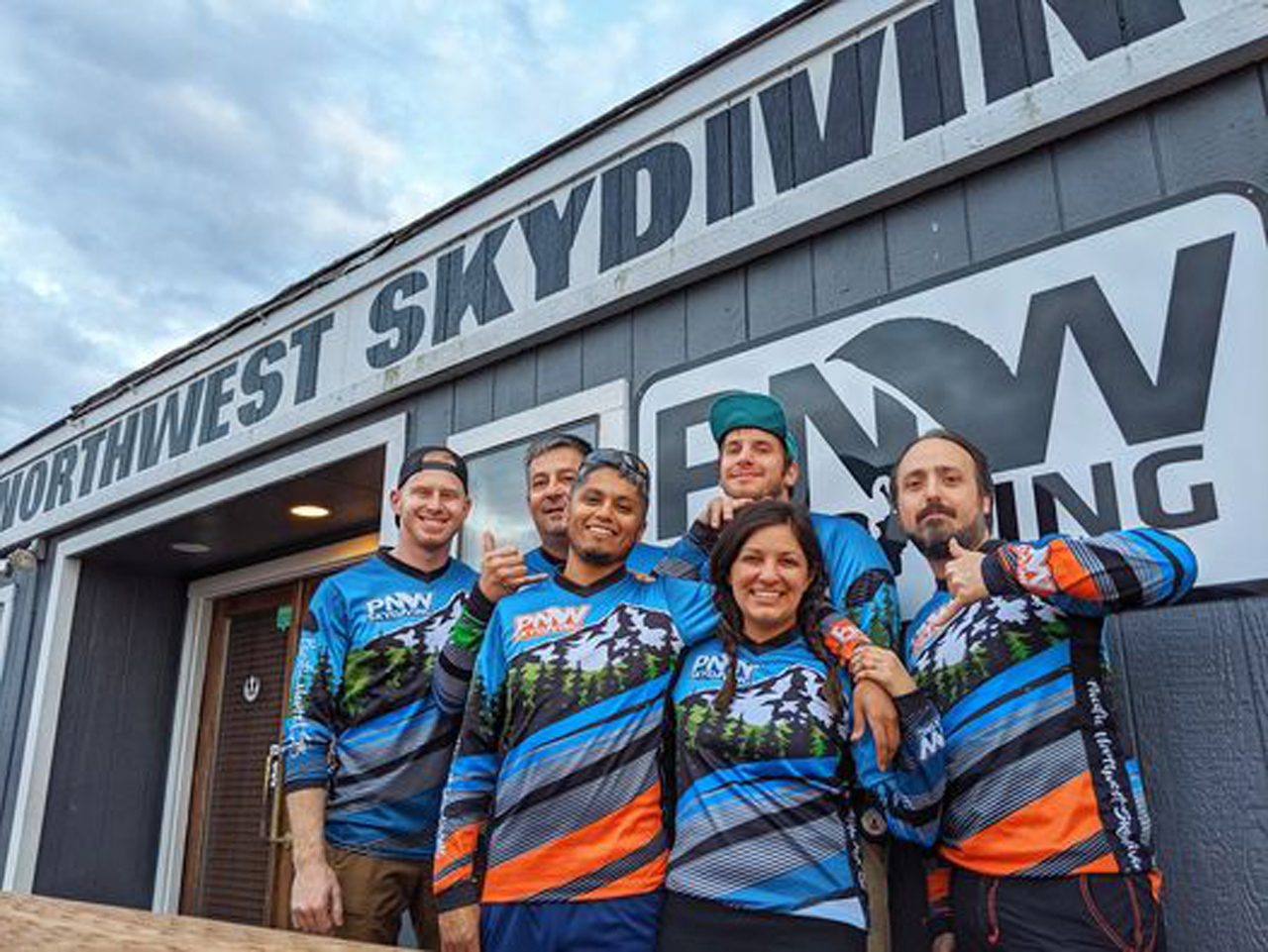 A group of licensed skydivers wearing matching shirts outside the PNW Skydiving hangar