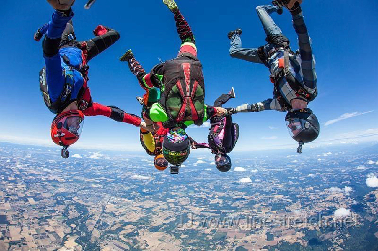 Small group of experienced skydivers in head down formation