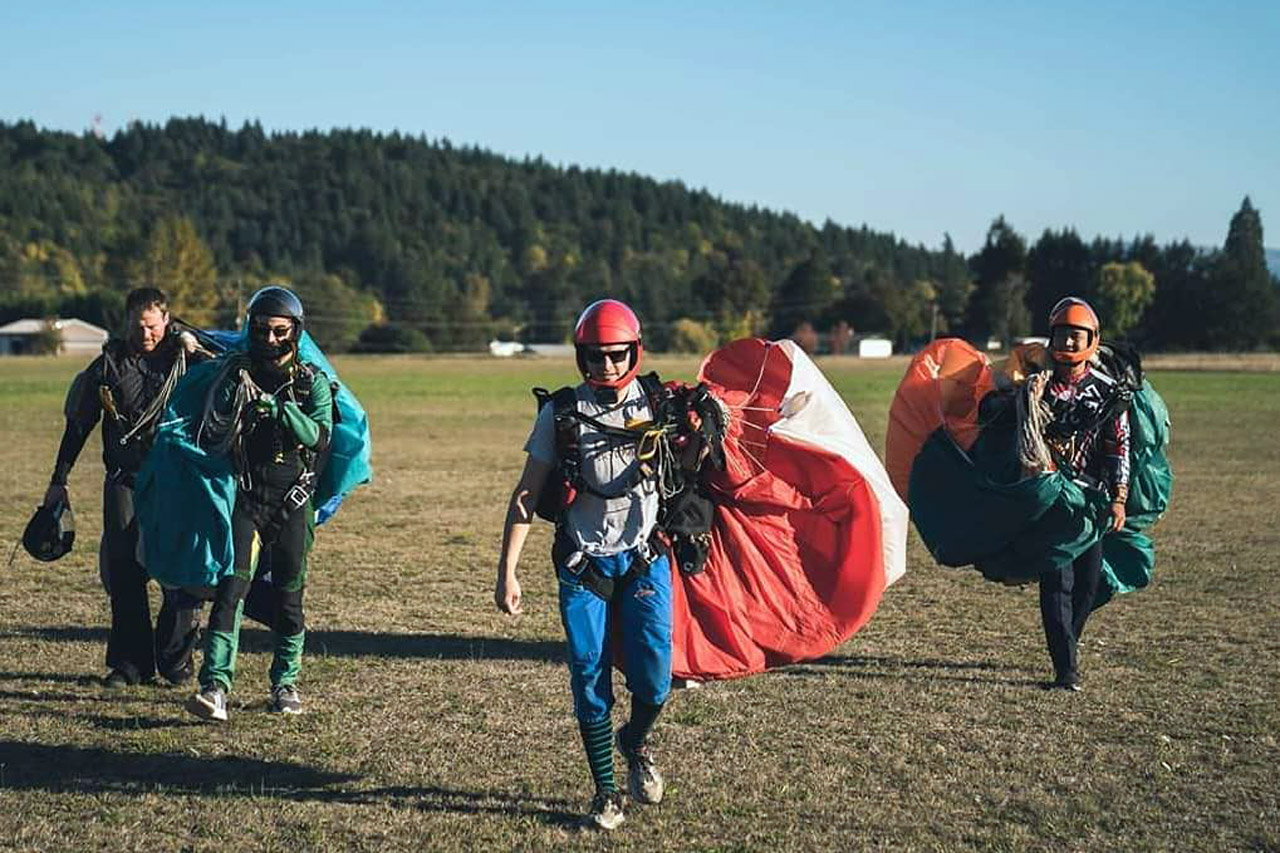 Experienced skydivers walking in the landing area with their gear after a jump