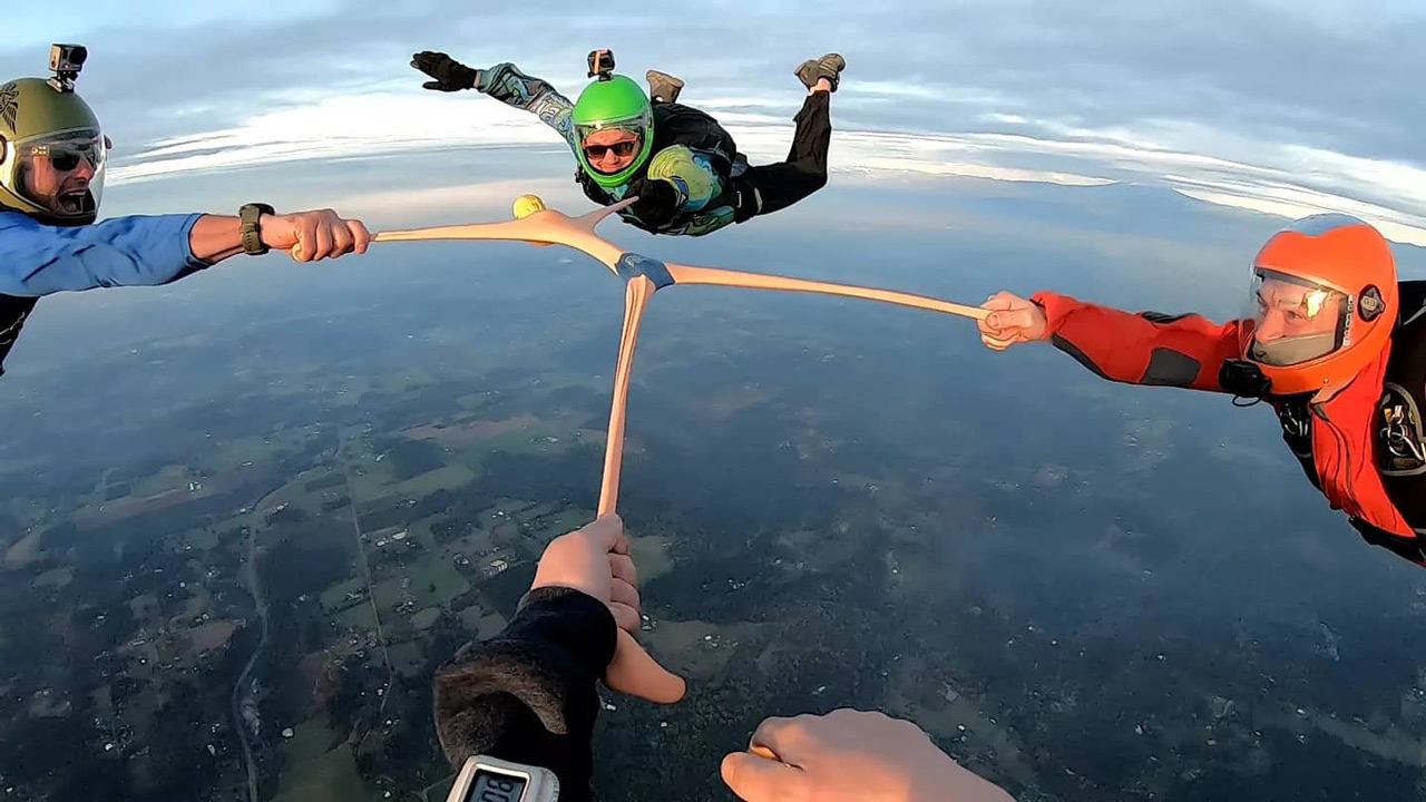 Four licensed skydivers in freefall holding a stretchy toy