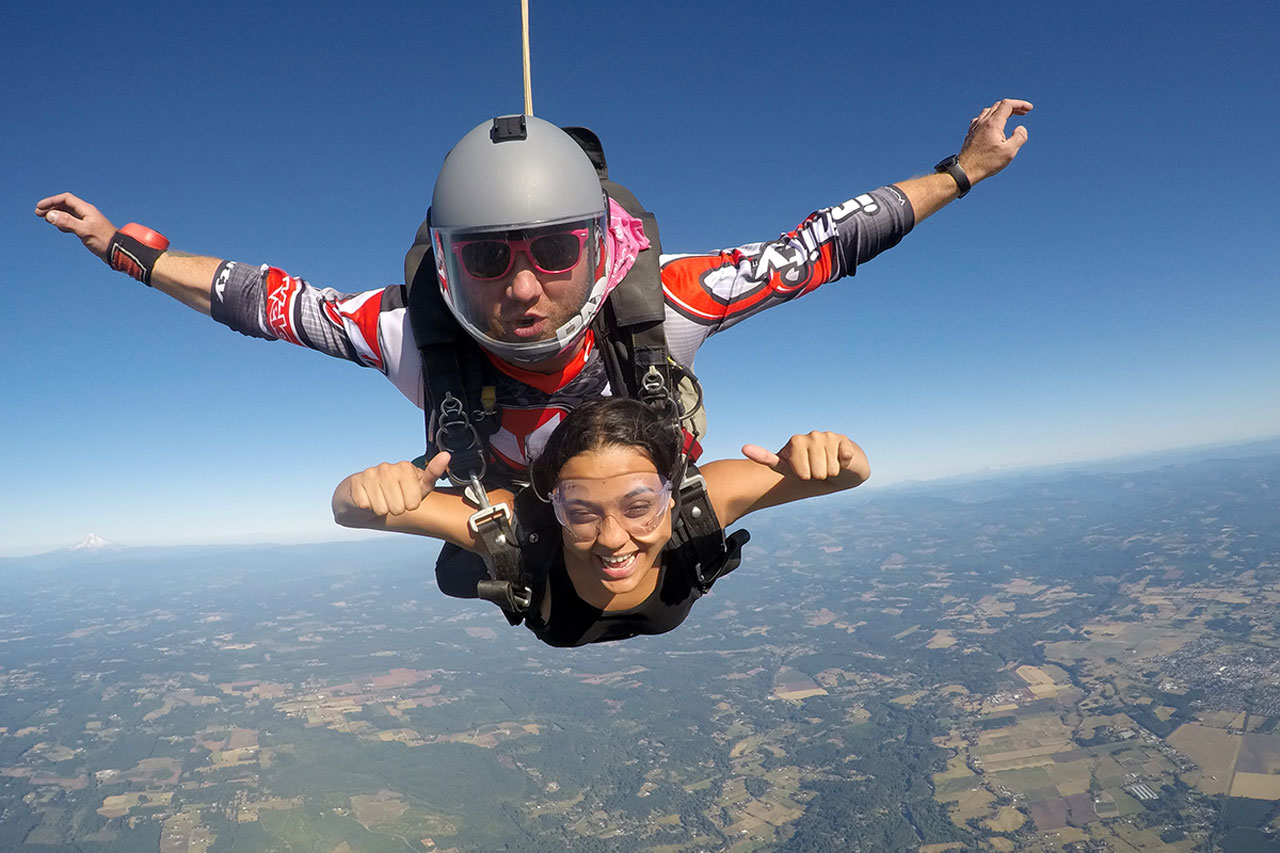 young woman gives thumbs up during freefall