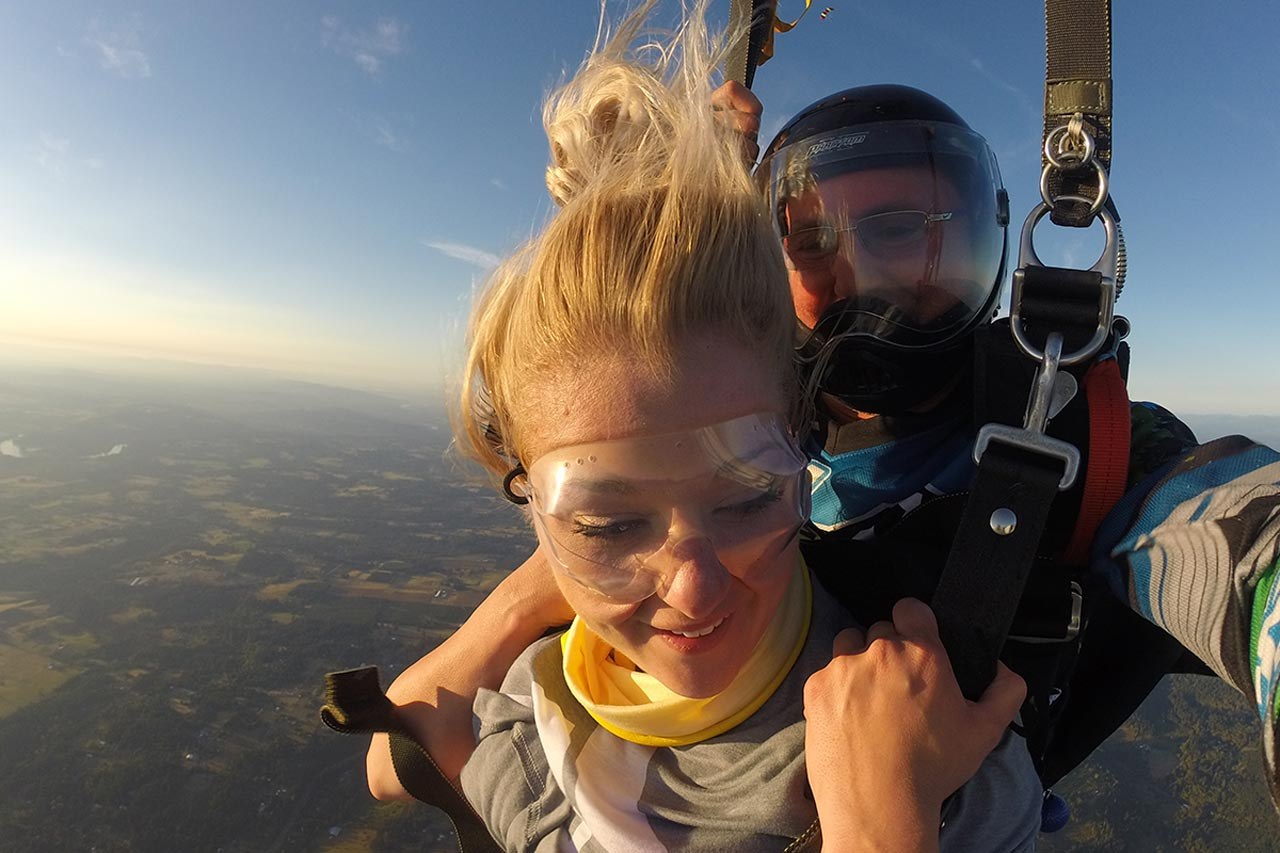 young woman looks down while flying under canopy