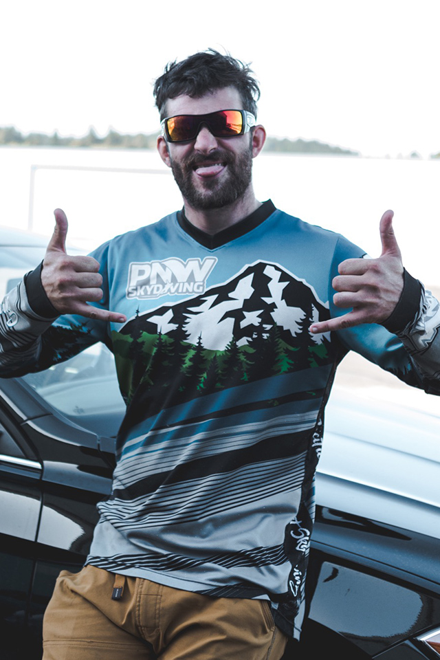 Kevin Rieschel smiles at camera wearing PNW Skydiving jersey