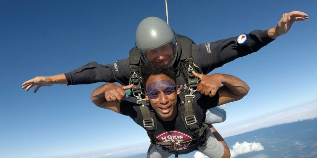 young man gives thumbs up in skydiving freefall
