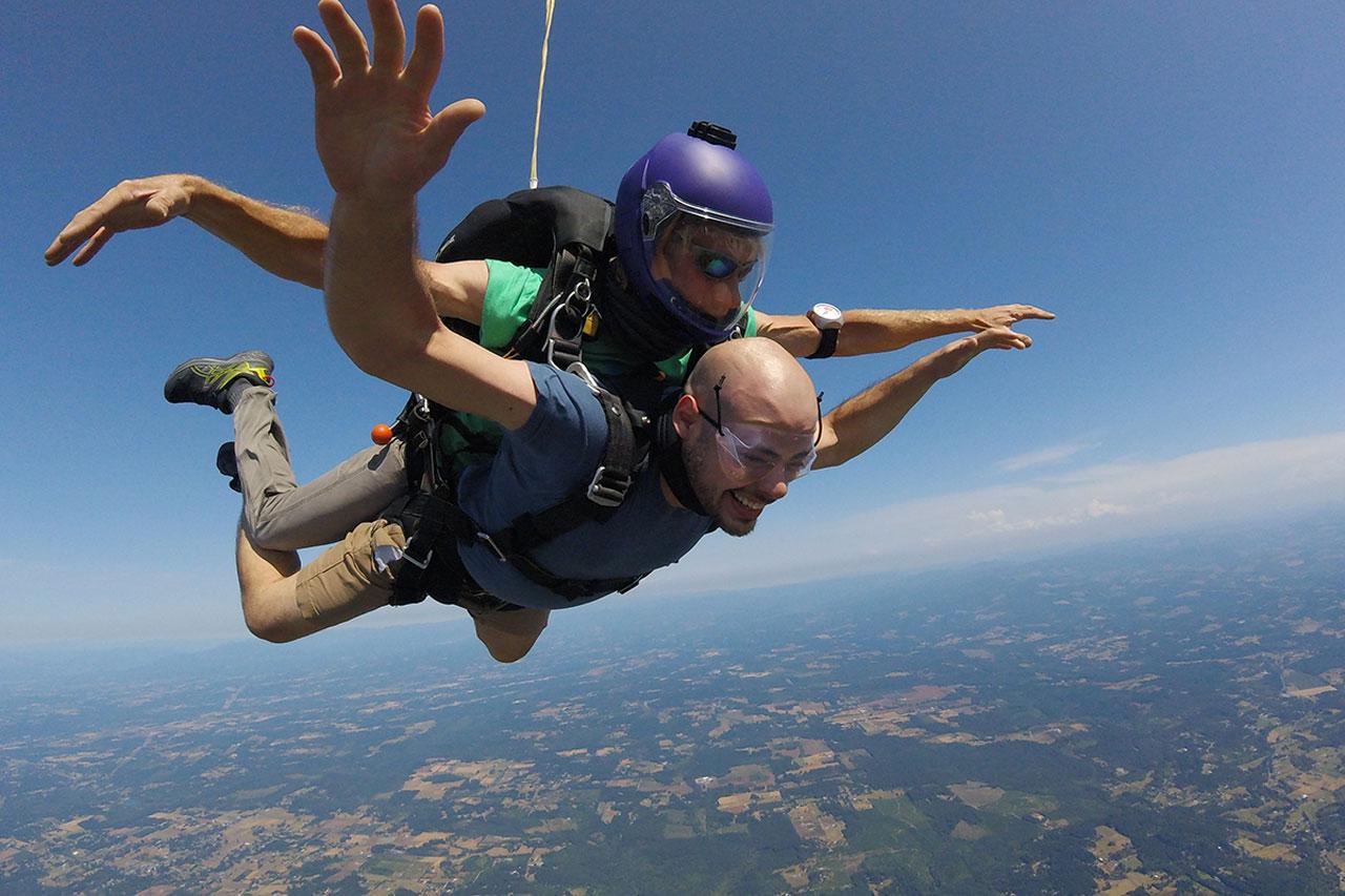 man smiles in skydiving freefall