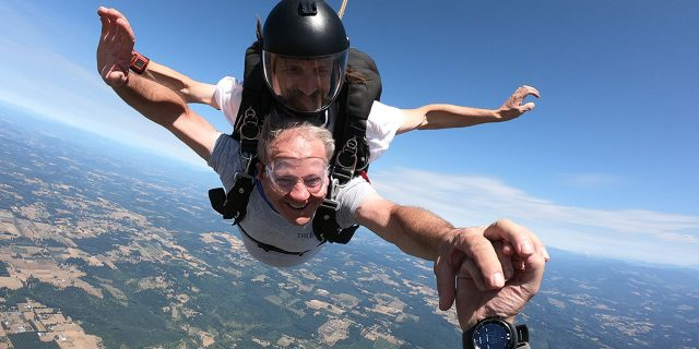 older gentleman smiles in freefall while grabbing camera flyers hand