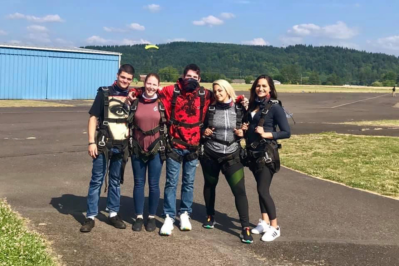 Group of friends taking a photo before tandem skydiving at PNW Skydiving