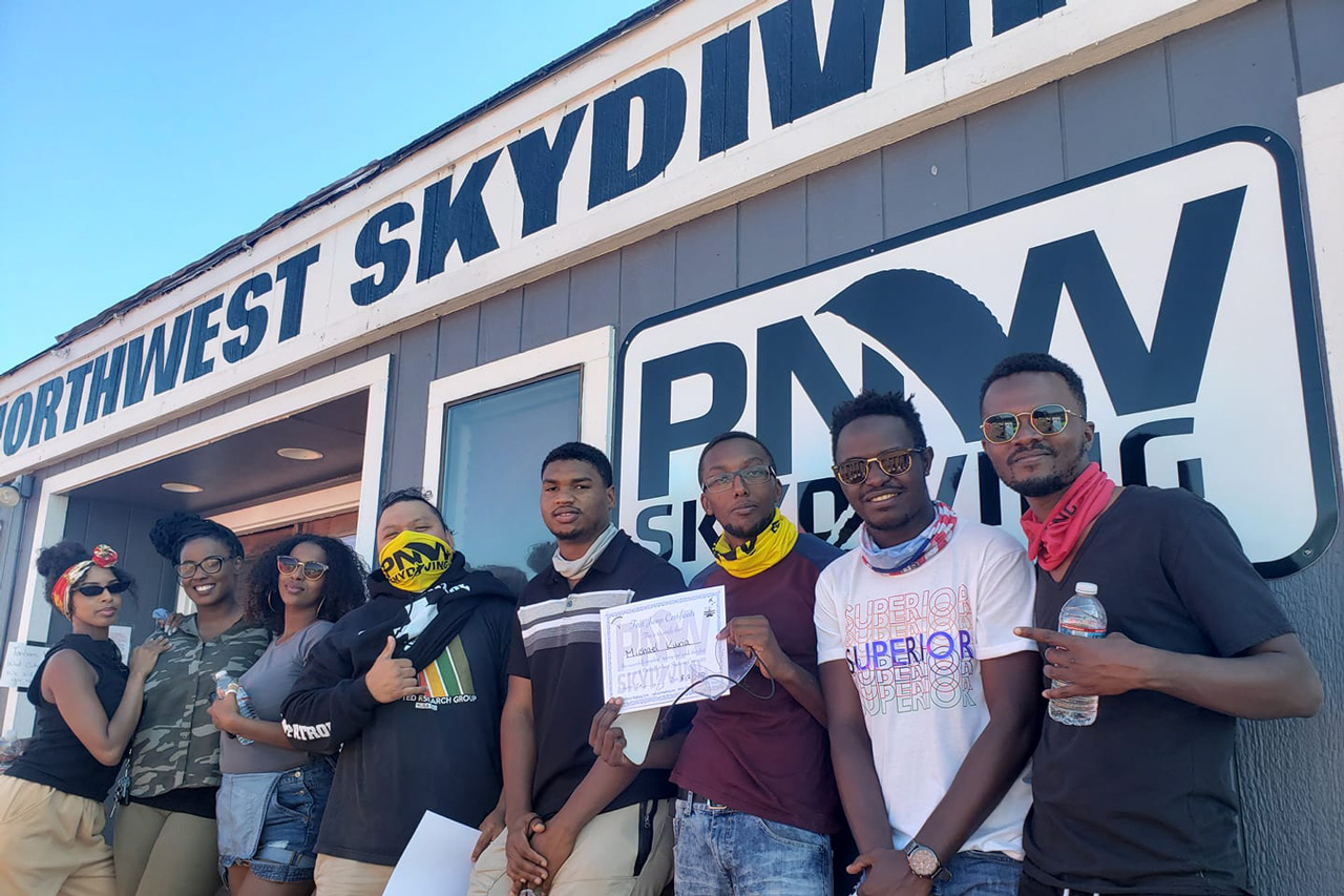Group of friends posing for photo outside PNW Skydiving Center hangar