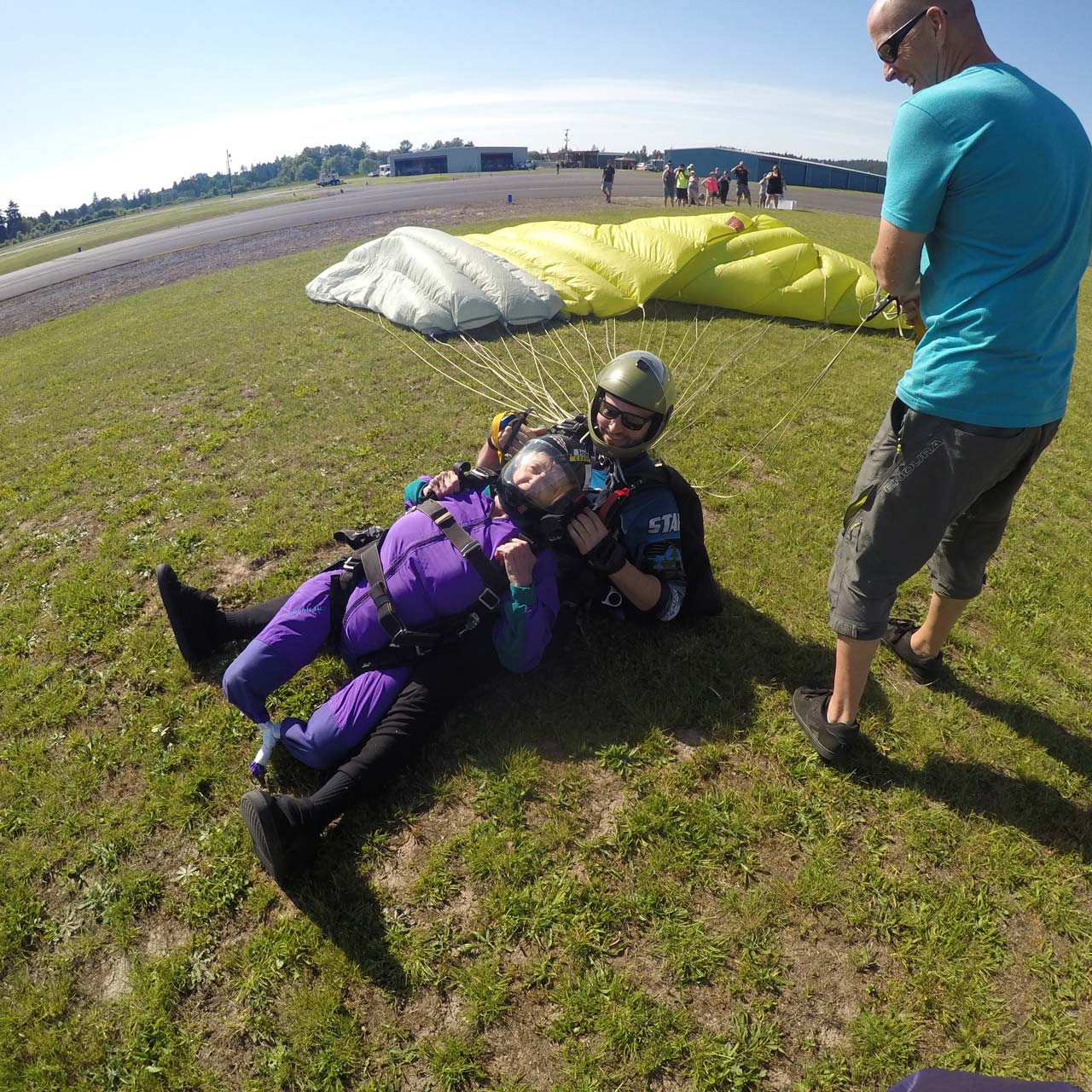 Disabled female tandem skydiving student landing in grass with instructor at PNW Skydiving in Oregon