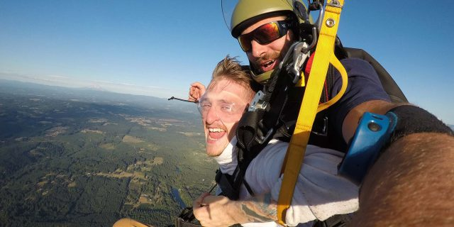 Smiling male tandem skydiving student and instructor under canopy above Pacific Northwest Skydiving Center in Oregon