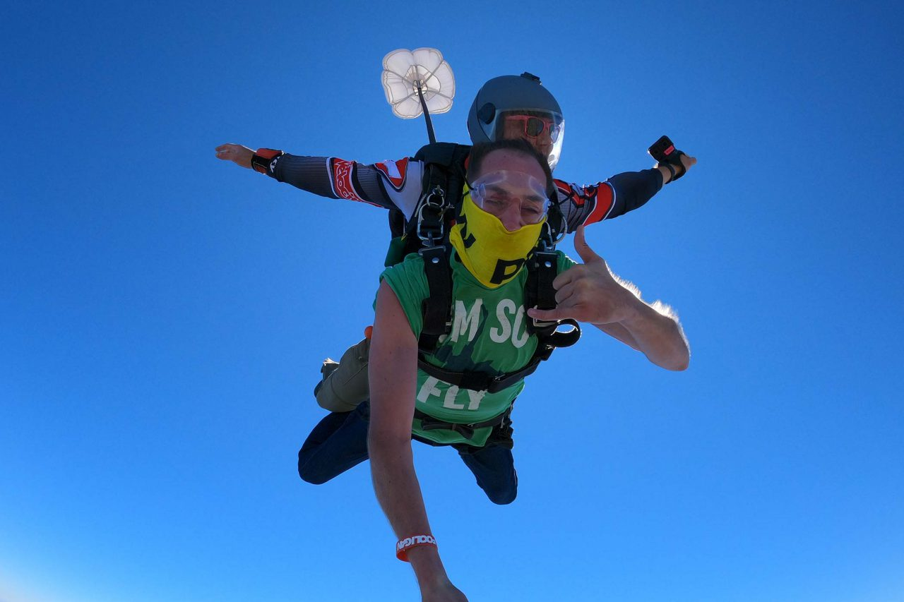 Male tandem skydiving student in freefall giving rock on hand signal with blue sky background
