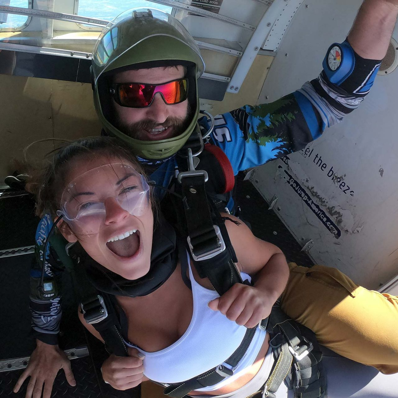Smiling female tandem student and instructor in doorway of aircraft above PNW Skydiving in Oregon