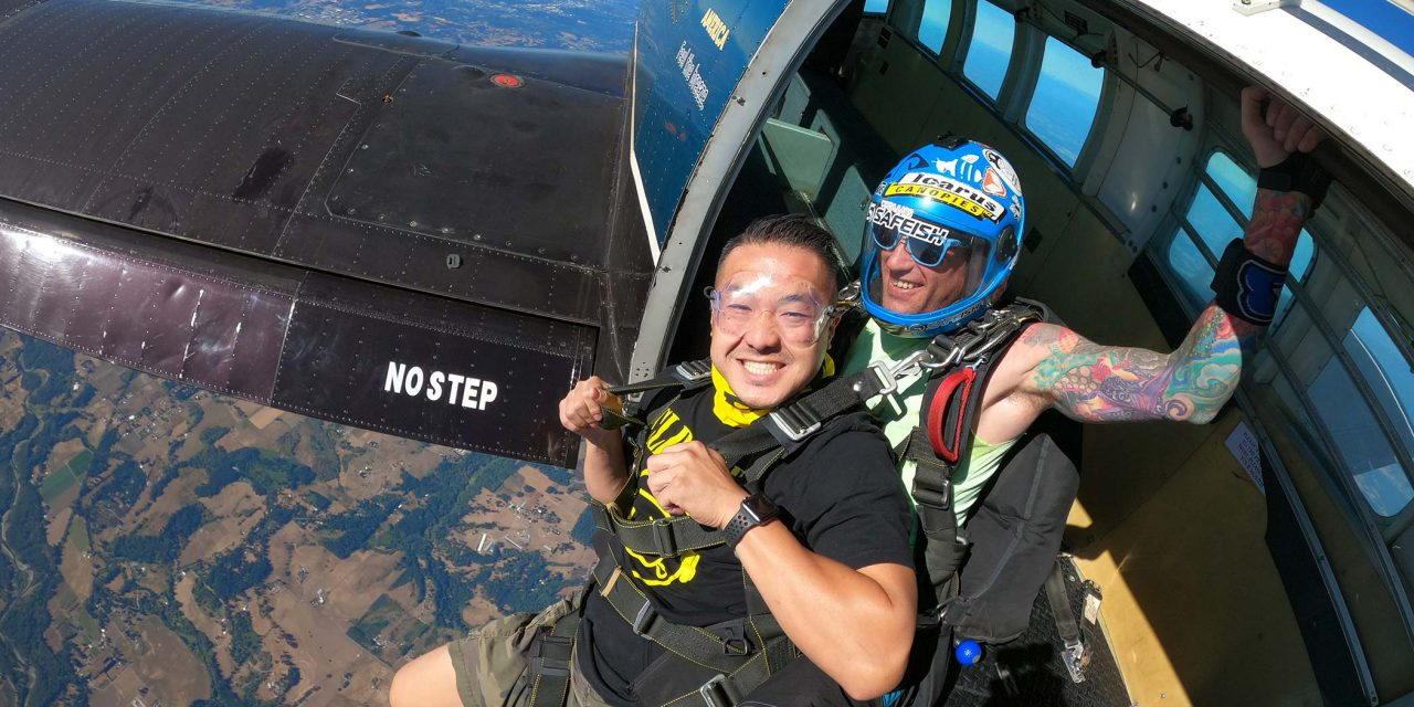 Male tandem skydiving student and instructor exiting aircraft above PNW Skydiving Center near Portland, OR