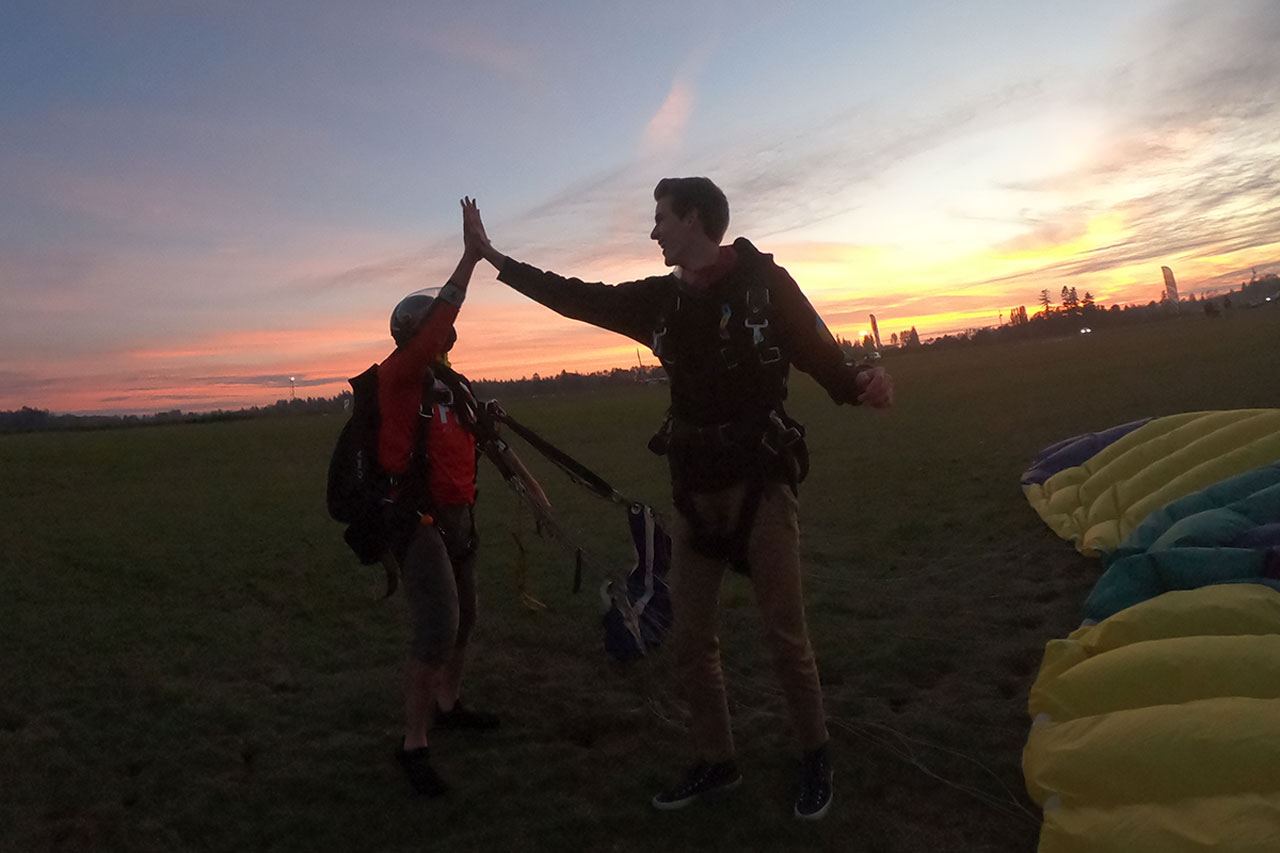 tall male tandem skydiver high fives his instructor at sunset
