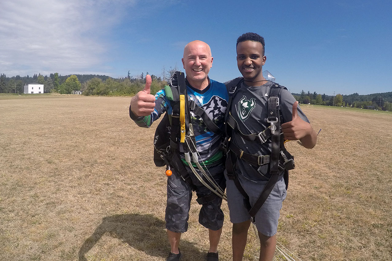 male skydiver embraces instructor and gives thumbs up in landing area