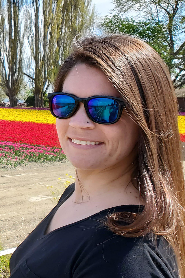 Victoria Connel smiles in front of bed of red and yellow flowers